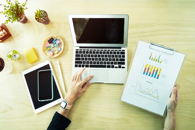 Closeup de pessoa trabalhando com laptop, tablet, celular e papel gráfico na mesa no escritório