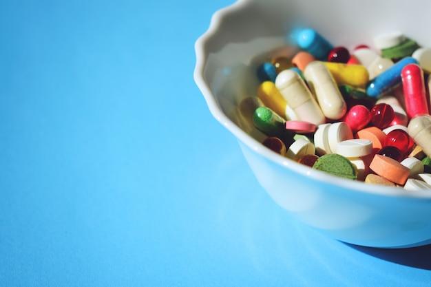 Closeup de pílulas, comprimidos e cápsulas de medicamento farmacêutico sobre fundo azul