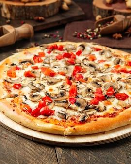 Closeup de pizza com cogumelos e tomate na mesa de madeira