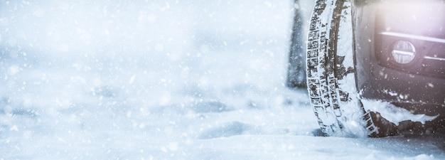Closeup de pneus de carro em uma estrada de neve. neve no banner panorâmico de estrada.