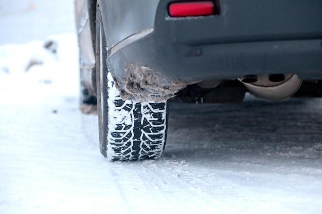 Closeup de pneus de carro no inverno na estrada coberta de neve.