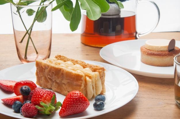 Closeup de porções de bolos, frutas frescas e bule na mesa