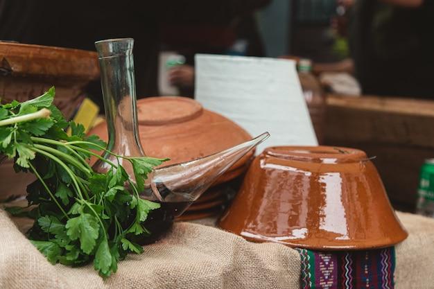 Closeup de potes de barro e erva na mesa sob as luzes com um fundo desfocado
