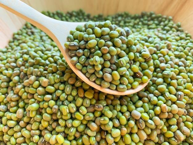 Closeup de qualquer mungbean ou feijão verde em uma colher de pau em uma tigela de madeira