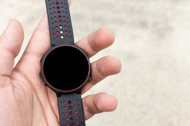 Closeup de relógio inteligente na mão do homem com tela em branco para mock-up