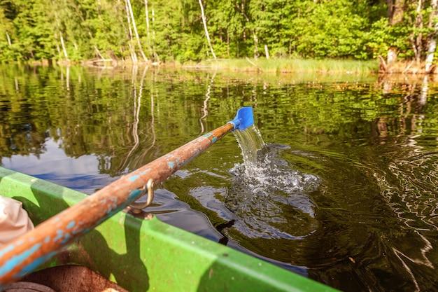 Closeup de remo de barco a remo movendo-se na água em um lago verde com ondulações