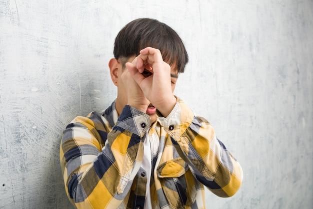 Closeup de rosto de jovem chinês fazendo o gesto de uma luneta