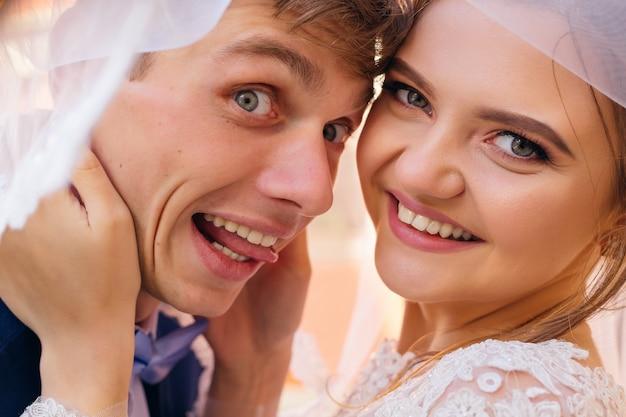 Closeup de rostos de recém-casados sob o véu de casamento, o noivo mostra a língua e a noiva sorri