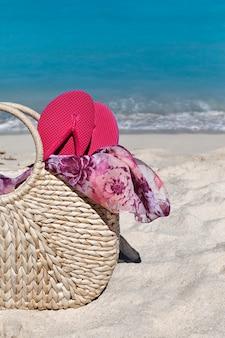 Closeup de saco de palha de verão com chinelos na praia