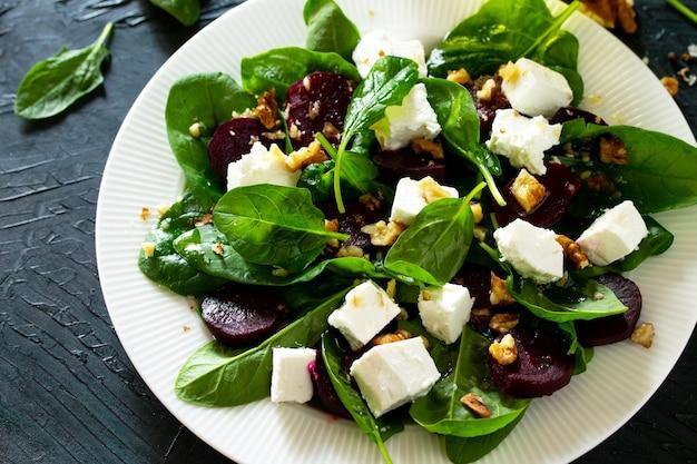 Closeup de salada com espinafre, queijo feta, beterraba e molho de óleo vegetal de nozes vitamina