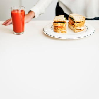 Closeup de sanduíche e suco na mesa branca