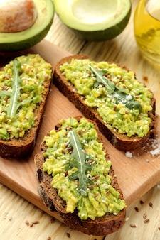 Closeup de sanduíches de abacate e rúcula na mesa de madeira natural. sanduíche com purê de abacate.