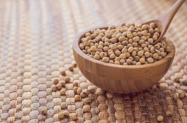 Closeup de sementes frescas de soja seca em uma tigela de madeira com uma colher