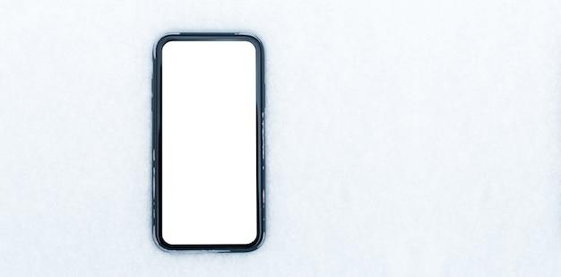 Closeup de smartphone com maquete em fundo de neve. vista superior do banner panorâmico. copie o conceito de espaço.