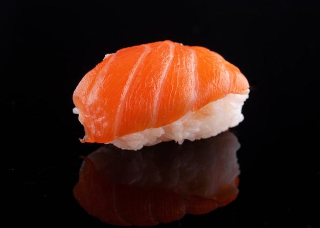 Closeup de sushi em um fundo preto com reflexo