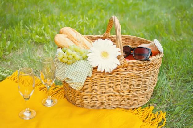 Closeup de taças de vinho na capa amarela, cesta de piquenique com comida e flor na grama verde