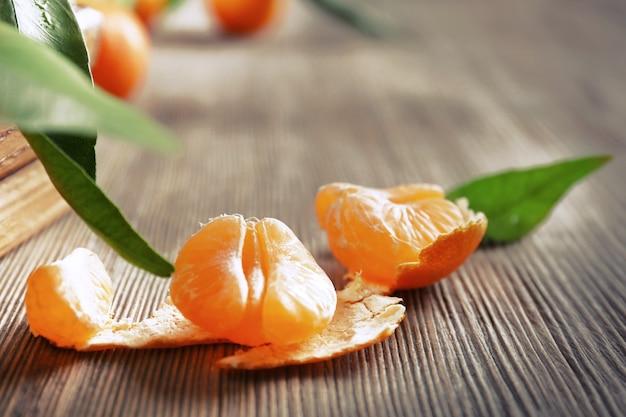 Closeup de tangerina fresca descascada em mesa de madeira