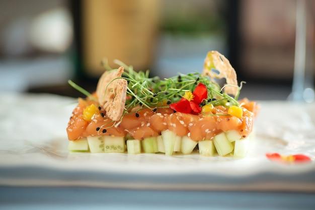 Closeup de tártaro de salmão espanhol em travesseiro de abacate em um prato branco