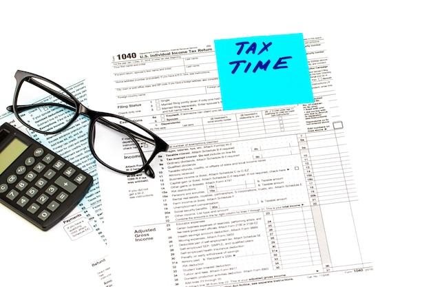 Closeup de tempo de imposto. escrito em um lembrete com formulário de imposto, calculadora e óculos