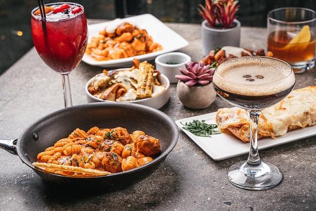 Closeup de tigelas de macarrão cozido com saladas, deliciosos coquetéis e vegetais fritos na mesa