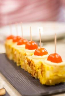 Closeup de típicos tapas de omelete espanhola e queijo com pinchos de cebola caramelizada em um bar