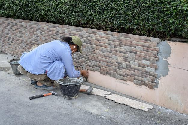 Closeup, de, trabalhador, cuidadosamente, instalar, parede cerâmica, azulejo, em, um, cola, enquanto, ladrar, um, parede