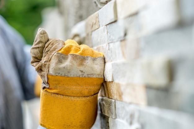 Closeup de trabalhador manual em luvas de proteção, azulejos de uma parede com azulejos ornamentais