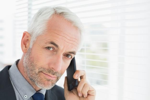 Closeup de um empresário maduro e sério usando o celular