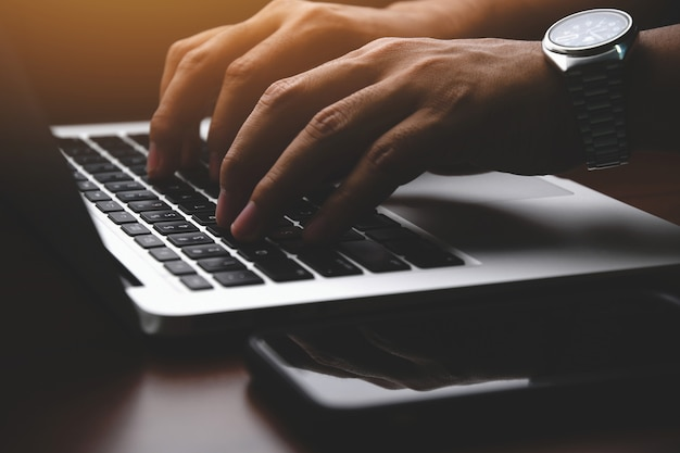 Closeup de um empresário mãos trabalhando e digitando no teclado do laptop