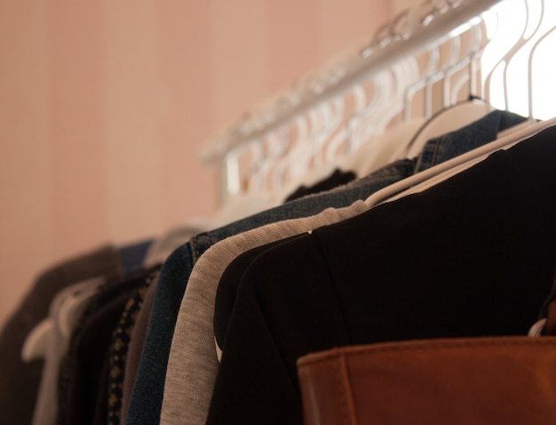 Closeup de uma bolsa de couro marrom e roupas penduradas em cabides brancos