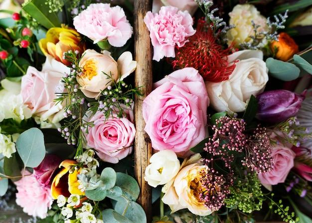 Closeup de variedade lindas flores na cesta de madeira