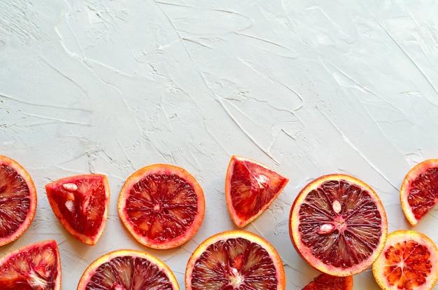 Closeup de vermelho siciliano sangue (sangrento) laranjas - cortado e fatiado, maduro e saboroso com copyspace, fundo cinza cimento