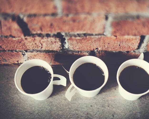 Closeup de xícaras de café com fundo de parede de tijolo