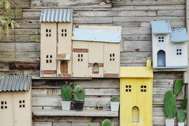 Closeup decoração na parede de madeira velha da casa por cacto e caixa de madeira em forma de casa