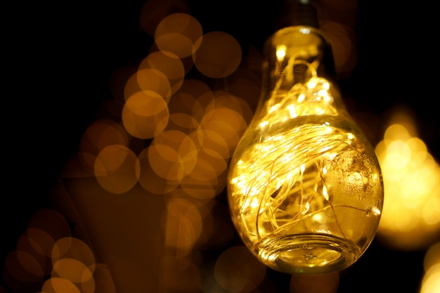 Closeup decorativo led luz na lâmpada vintage com ligar as luzes brilhando durante a noite e embaçada.