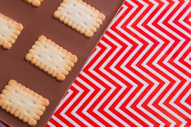 Closeup deliciosa barra de chocolate em fundo ondulado de vermelho e branco