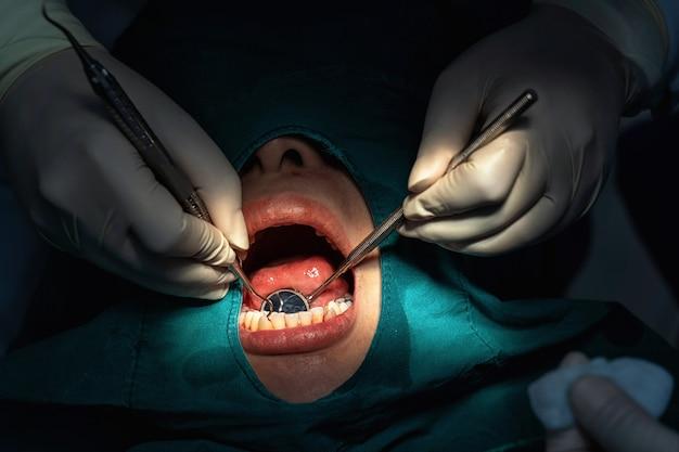 Closeup, dentista e assistente operando para verificação e limpeza dos dentes na clínica odontológica