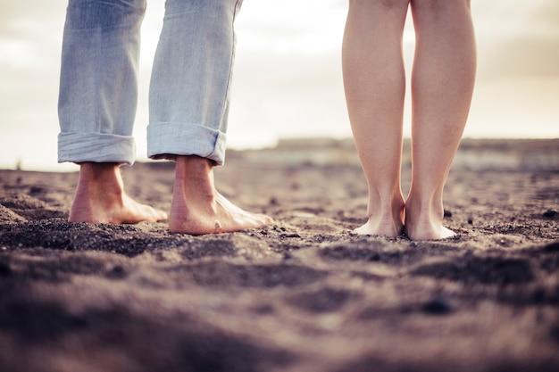 Closeup descalço dois pares de retrato de pés caucasianos na praia. visto por trás, amor e conceito íntimo para jovens juntos.