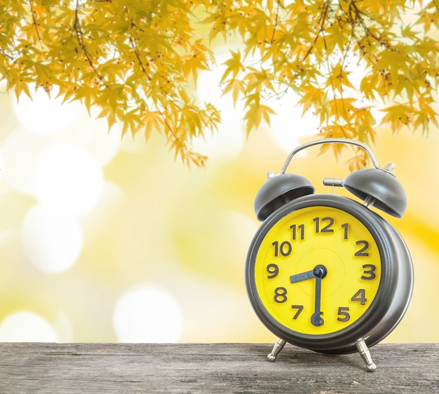 Closeup despertador mostrar o tempo em oito e meia na mesa de madeira