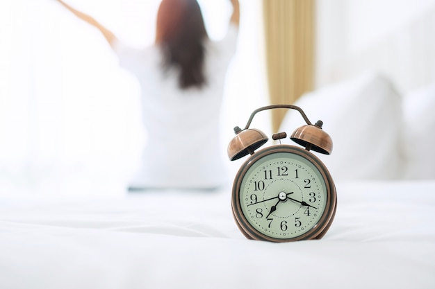 Closeup despertador na cama com mulher feliz, estendendo-se depois de acordar