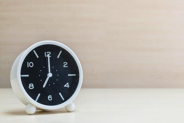 Closeup despertador para decorar em 7 horas na mesa de madeira e fundo da parede