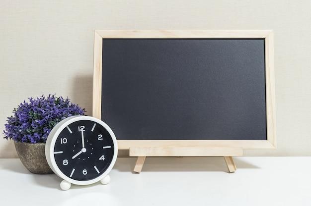 Closeup despertador para decorar mostrar 08:00 com placa de madeira preta na mesa de madeira branca