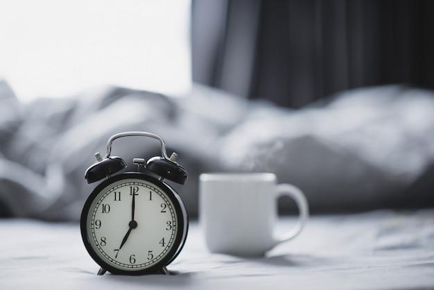 Closeup - despertador tenha um bom dia com uma xícara de café na cama à luz do sol da manhã.