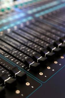 Closeup do console de mixagem de áudio, profundidade de campo