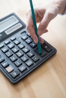 Closeup do contador pressionando o botão da calculadora