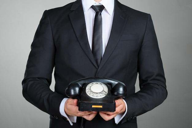 Closeup do empresário segurando um telefone receptor