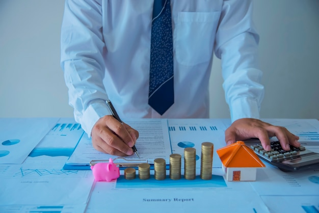 Closeup do novo proprietário assinando um contrato de venda de casa ou documentos de hipoteca com uma casa de brinquedo de madeira