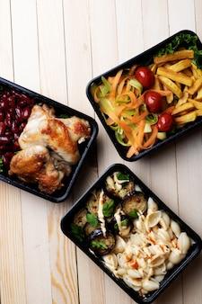 Closeup do prato principal, almoço em recipientes para alimentos, asas de frango assado, legumes no vapor, carne estufada, refeição pronta para comer
