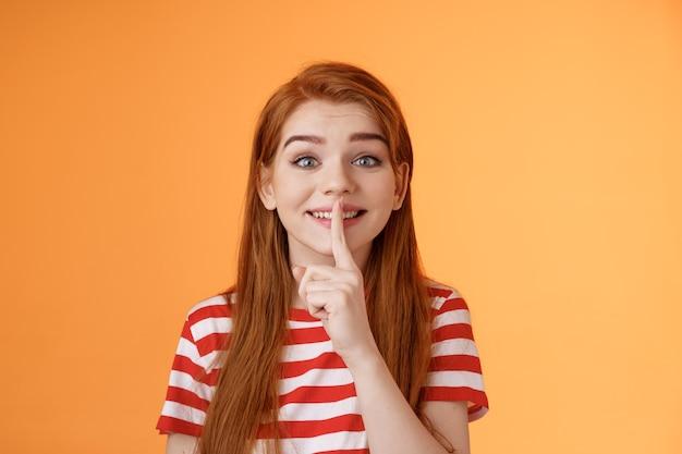 Closeup encantadora linda garota ruiva boba fazendo festa surpresa pegando promessa de amigos não contar ...