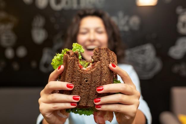 Closeup, engraçado, turvado, retrato, de, mulher jovem, segure, mordido, sanduíche